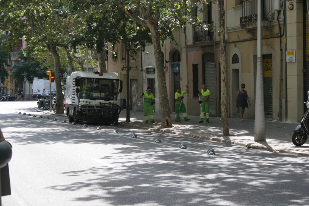 Barcelona Medi Ambient street cleaning crews clear sidewalk and curb line.